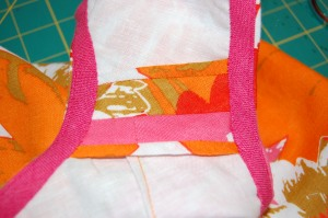 This shows a shoulder seam with a Hong kong finish to the raw edges and the pink bias binding around the armhole and neck.