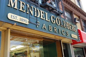 The distinctive sign for Mendel Goldberg Fabrics on Hector Street in NYC.