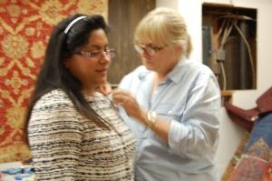 Susan fine-tunes the shoulders of Myra's jacket.