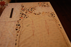 "The fabric is shown 35"" flat on my cutting table.  The muslin pattern piece for the front of the dress is on the right, and the two shortened back pieces are lined up smack against each other on the left.  The yoke pieces then fit above the dress front.  I did not need facings, as I lined the entire dress in a light weight linen/cotton blend, and finished the neck and armholes all by hand."