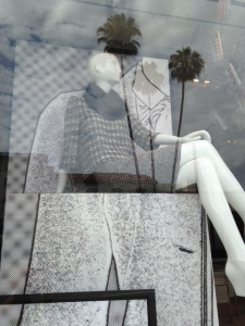 The reflection of palm trees in the window obscures some of the fashions.